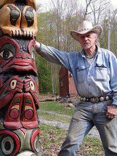 Johnny in front of lost Franks Place with the totem pole he carved Himself