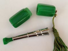 "Art Deco Chrome and bakelite small folding cigarette holder in tasseled bakelite case. Cigarette holder 5cm (2""). Case 4cm (1 5/8"")"