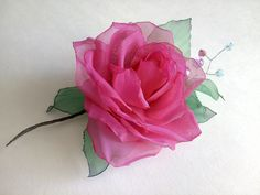 Very bright chiffon fuchsia color rose harmonically framed with a bright-emerald leaves and enriched with a twig made from bijouterie wire and beads. Thanks to fixation clasp the flower can be used not only as a hair-pin but as a brooch also: you can decorate a jacket with it, sweater or elegant blouse. Diameter of the rose near 2.5 inches (6.5 cm), the general length of the flower near 4.5 inches (12 cm).