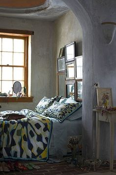 love the collection of mirrors and pictures above the bed. #anthropologie #bedrooms