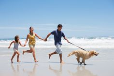 Imagen libre de derechos: Family with dog running on beach