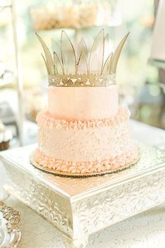 A two-tier pink wedding cake with a crown topper | Brides.com