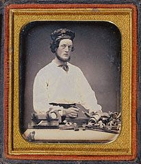 Unknown   American, about 1848   Hand-colored daguerreotype   For his daguerreotype portrait, this carpenter chose to be shown with the tools of his trade. Curlicues of wood shavings suggest actual work in progress, but the static quality of his pose and the blank backdrop indicate that the portrait was made in the photographer's studio rather than the carpenter's workroom.