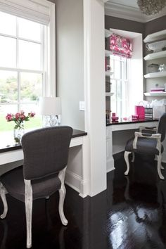 Chic gray & pink office for two with creamy gray walls paint color, built-in floating twin desks, gray linen upholstered French chairs with silver nailhead trim, Pottery Barn Capiz Pendant, glossy ebony wood floors, white floating shelves, pink & gray ikat roman shades and pink accents.