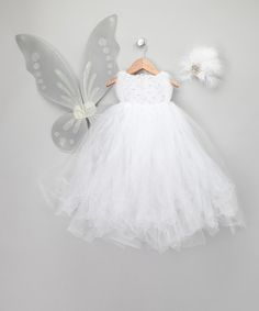 """Kissed with sparkles and blossoming with fairy feathers, this enchanting set casts a magical glow. Boasting a cloud of poufy tulle, satin-strapped wings, and a matching frosty white clip, these pretty USA-made pieces are ready to whirl and twirl to the """"Waltz of the Snowflakes.""""Includes dress, wings and clipTulle / ribbon"""