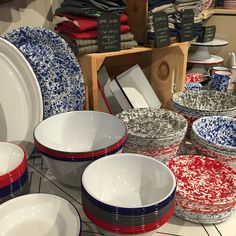 A glimpse inside the shop: modern enamelware in both vintage color rim and marbleware styles with a backdrop of USA made Hedley & Bennett aprons. Onemercantile.com