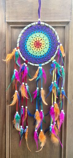 Rainbow ratan dreamcatcher with rainbow feathers handmade in Bali, Indonesia.
