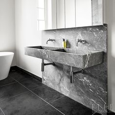 Slabs of richly veined marble create a splashback that marries with this 'his and hers' wall-mounted basin in the same material. The dual-purpose cabinet provides a mirror-cum-storage in a compact space above. Large format floor tiles, despite being black, help to draw the eye across the room to create a sense of space.  Photography: Sisters Agency