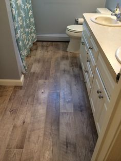 Installed with chamois grout, Adura® Distinctive Plank Dockside (Sand color) luxury vinyl flooring sure makes a splash in this bath!