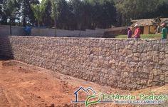 Muro de contenção feito com pedra bruta, vencendo altura de arrimo de mais de 2 metros