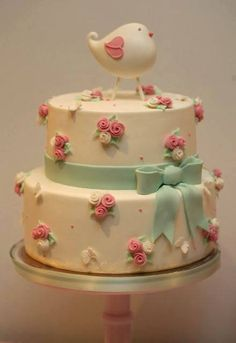 Sweet cake with rose bunches, blue ribbon and bird topper