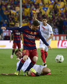 Sevilla's Polish midfielder Grzegorz Krychowiak (bottom) tackles Barcelona's Argentinian forward Lionel Messi during the Spanish…