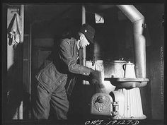 Conductor George E. Burton building a fire in the stove of the caboose on the Atchison, Topeka and Santa Fe Railroad enroute to Chillicothe, Illinois, 1940s.  Photo by Jack Delano. LOC