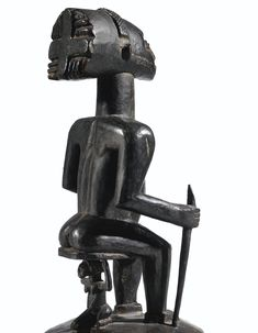 Statue, Hemba, République Démocratique du Congo haut. 33 cm  - Cette très rare effigie d'ancêtre Hemba se distingue par son iconographie : assis sur un siège cariatide dont le plateau circulaire est soutenu par un personnage féminin aux traits similaires. La dignité de la pose, exaltée par la cambrure du dos mettant en valeur l'ampleur de la coiffure cheffale, est accentuée par le sceptre tenu dans la main droite.