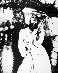 By Lillian Bassman : Untitled, Model With Raincoat And Umbrella, 1950.