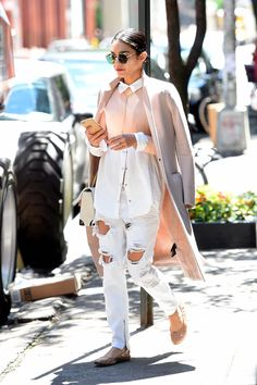 Near perfection, she styles her pink and white, color-blocked button-up shirt with a pink coat worn on the shoulders and distressed white denim. - MarieClaire.com