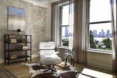 "As soon as you enter, a comfortable Eames Lounge chair invites you in, giving her back to a solid brick wall adorned by the ""cappucino"" art photography piece by Francis Augustine and surrounded by flowing linen taupe window drapes and a shiny cowhide rug."