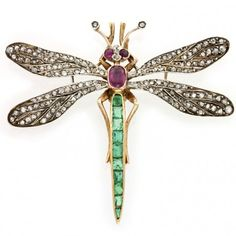 An emerald, ruby and rose-cut diamond dragonfly brooch, the two pairs of pierced veined wings pavé-set with rose-cut diamonds, silver-set to a yellow gold mount, the body set with an oval faceted ruby with faceted emerald-set tail, with ruby and diamond head and antennae, all mounted on gold, gross weight 10.6 grams