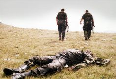 Two Bosnian Croat soldiers pass by the corpse of a Bosnian Serb soldier