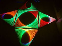 Large colourful string art piece under UV lighting