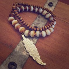 "Beaded stretch bracelet feather charm ~ boho Beautiful stretch bracelet - larger beads are glass and the smaller is wood - accented by silver feather charm and is almost 2"". Really pretty combination of browns. Three Bird Nest Jewelry Bracelets"