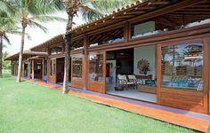 Esse projeto é inspiração para casa de campo, sítio ou fazenda. Grandes portas de madeira e vidro se abrem e deixam a decoração interna integrada com o grande gramado da fachada.