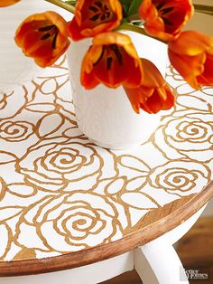 White paint applied over a floral stencil showcases a little wood grain and highlights the table's pretty lines while hiding its imperfections. Finish the surface with a water-base acrylic sealer for protection.