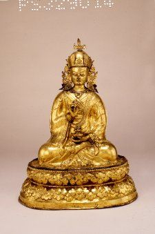 A figure of Padmasambhava seated on lotus throne; holding a vajra and purnaghata (vase of life); features a sun-moon symbol, representing transcended duality, on his hat. (British Museum)