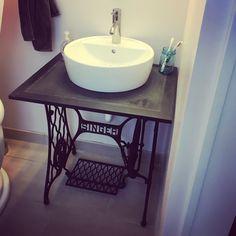 Old sewing machine base turned into bathroom vanity with vessel sink.
