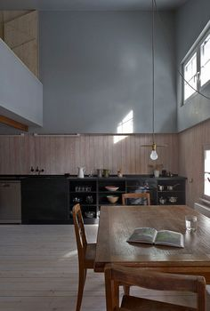 jonathan-nathan-tuckey-design-gives-old-buildings-a-new-life. Modern kitchen design. Wood table. Modern lamp. For more inspirational ideas: http://www.bocadolobo.com/en/inspiration-and-ideas/