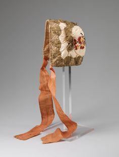 Child's cap, Norway, 1750-1790. Cream silk brocade, metall lace decoration, orange silk ribbon binding.