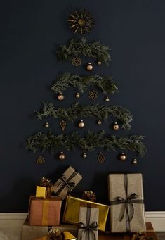 a stylish wall mounted Christmas tree on a black wall of evergreens, lights and brass ornaments Natural Christmas Tree, Wall Christmas Tree, Alternative Christmas Tree, Christmas Tree Decorations, Christmas Fun, Christmas Ornaments, Diy Wand, Mur Diy, Deco Originale