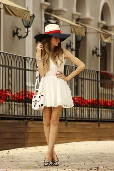 Navy outfit wearing white dress and big hat with striped shoes. Main point of the outfit is the Pandora Jewelry with travel inspiration charms.