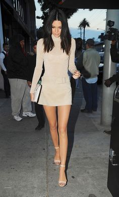 Kendall Jenner wears a lurex nude turtleneck, suede miniskirt, and ankle-strap heels