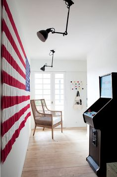 """""""Old Glory"""" #flag highlighted by repurposed desk lights. What's not to love about a vintage arcade game in the hall (by Sarah Lavoine)"""