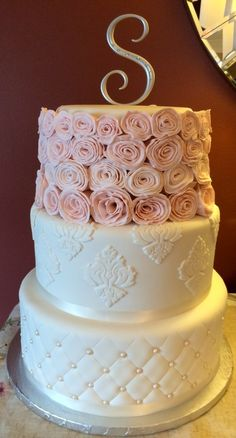 All white cake with pink rosettes made by Joli Gateau