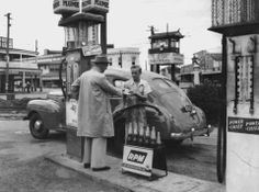 Filling the car with petrol at the Fiveways, Woolloongabba, 1949