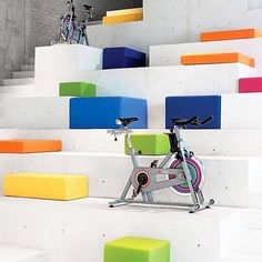 Mexico City's indoor cycling devotees received a welcome facility with Síclo, a street-level fitness temple by Cadena + Asoc Concept Design and Rojkind Arquitectos. Glass fronts render the interior almost a public space, where passersby can marvel at a stepped concrete monolith (a not-so-subtle reference to ancient Mexican architecture) furnished with bright, energetic cushions for resting and stretching. Photography by Jaime Navarro. #architecture #interiors #design #interiordesign #fitness…