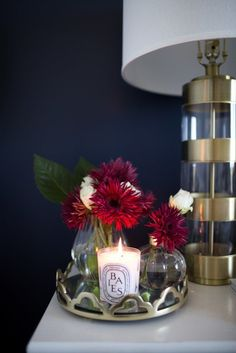 A dresser with a gold lamp, a candle, and flowers