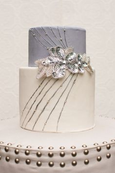Beautiful cake with silver glitter flowers. The art deco lines and glitter make it perfect for a #greatgatsby wedding