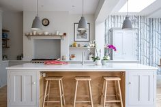 Shaker style kitchen painted in Farrow & Ball Pavilion Gray with Bianco Venato engineered quartz worktop. The island has a built in breakfast bar with beech stools. The three hanging pendant lights adds a subtle touch of colour. Floating oak shelves and oak mantelpiece display beautiful ceramics.