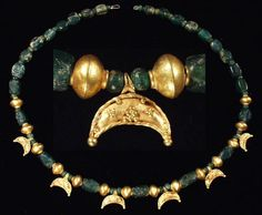 "ROMAN GOLD AND GLASS NECKLACE           II-III century A.D.  Composed of six gold crescent pendants with twisted wire perimeter and double-ribbed suspension loop,  triangular clusters of granulation, single granules at termination points; twenty- five 14-faceted green glass beads; thirty-four spherical and semi-spherical small green glass beads and later gold beads, soldered from two halves and terminated with wire collars;  L. 15"" (38.1 cm)."