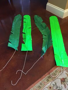 "Palm and banana tree leaves using wire coat hangers and green and lime green duct tape made for ""Journey Off the Map"" VBS. Took 3 stripes of tape overlapping slightly, then placed straightened hanger in center, then covered with 3 more strips of tape. Trimmed bottom, made a rounded edge at the top, then cut diagonal cuts all the way down. Once bent, makes the perfect Palm or banana leaf! (PS. I got 7 leaves from 2 rolls of the dark green but only 5 leaves from the lime green tape.) These…"