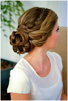 A deep side part with a braid and two loose twists cascading back into a curly bun. Chic!
