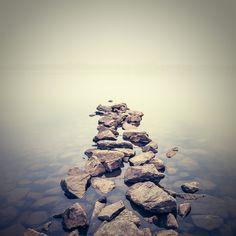 Rannan kivet muodostavat kauniin sillan, jonka takaa avautuu sumuinen järvi. Tämän kuvatapetin tunnelma ja värit luovat rauhallisen tunnelman.