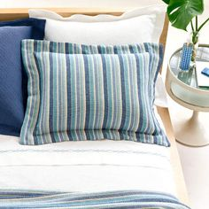 Give your bed a texture lecture with woven coordinates, matelassés and shams in blue and white, plus a striped blanket in complementary colors.