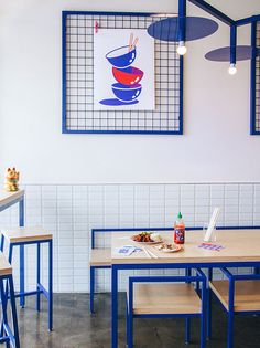 A custom made, blue zig-zag light fixture hangs in the middle of this modern restaurant tying together the overall look of the furniture and decor. White subway tiles partially cover the walls, while blue metal grid frames with graphic artwork, adds a unique decor element that can be easily changed out.