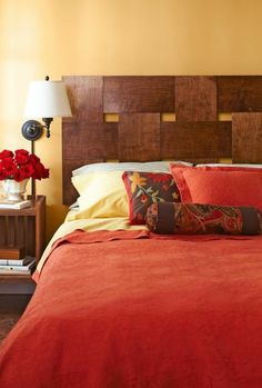 schlafzimmergestaltung bettgestell dunkles holz kopfteil rote bettwäsche kissen
