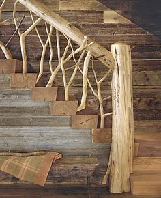 The Adirondacks country house's main staircase railing is crafted from tree branches and logs. Notice the use of a variety of natural woods in the unfinished wood walls and the rough hewn wood block stairs.