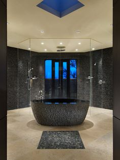 Contemporary Master Bath with carved stone vessel tub, and a full glass shower with a view...